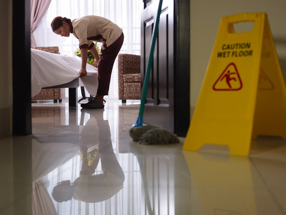 Asian maid tidying up bed and cleaning luxury hotel room with a caution wet floor sign