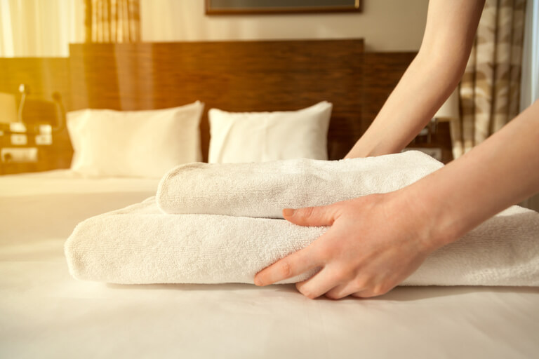 Close-up of hands putting stack of fresh white bath towels on the bed sheet. Room service maid cleaning hotel room. Lens flair in sunlight
