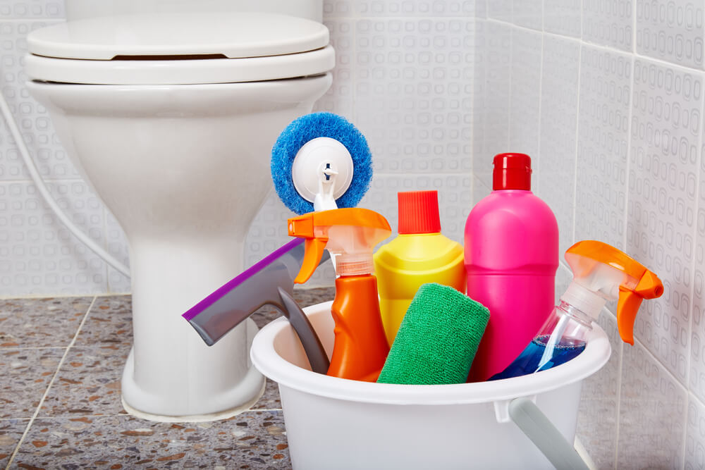 Close up view of House cleaning colorful products and tools in white bucket on tiled floor in toilet