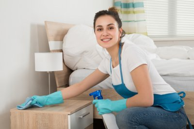 Happy Female Housekeeper Cleaning Nightstand In Room with turquoise gloves
