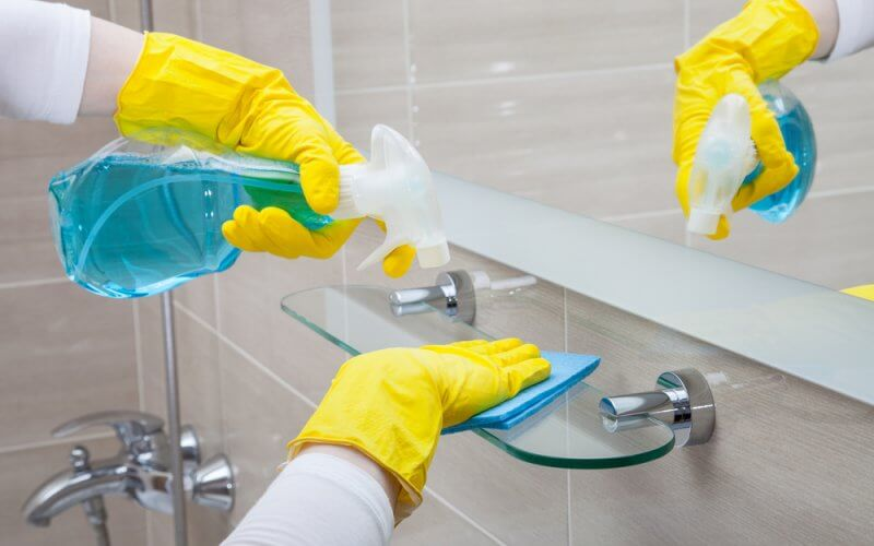 Housemaid wearing yellow gloves cleaning the bathroom