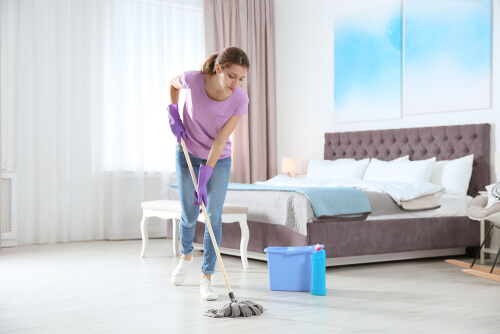 Young woman washing floor with mop in bedroom