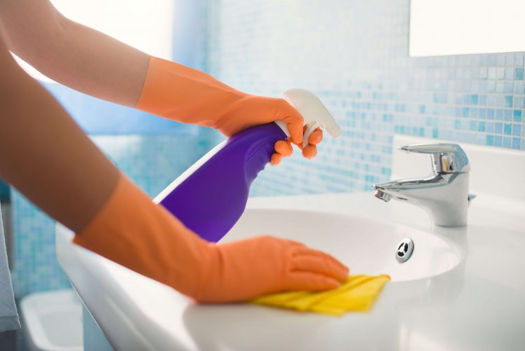 woman doing chores in bathroom at home, cleaning sink and faucet with spray detergent
