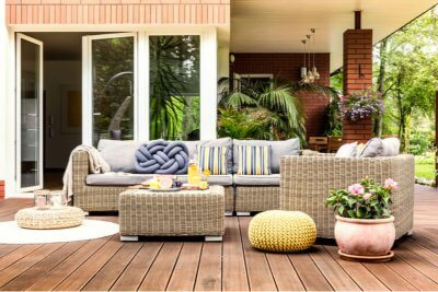 Beige garden furniture with striped pillows on a wooden terrace with pink flowers and poufs