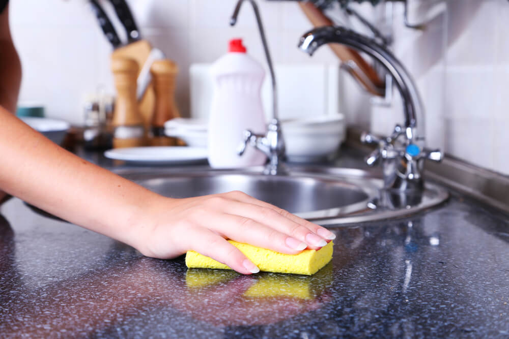 Using hands to clean kitchen with yellow sponge