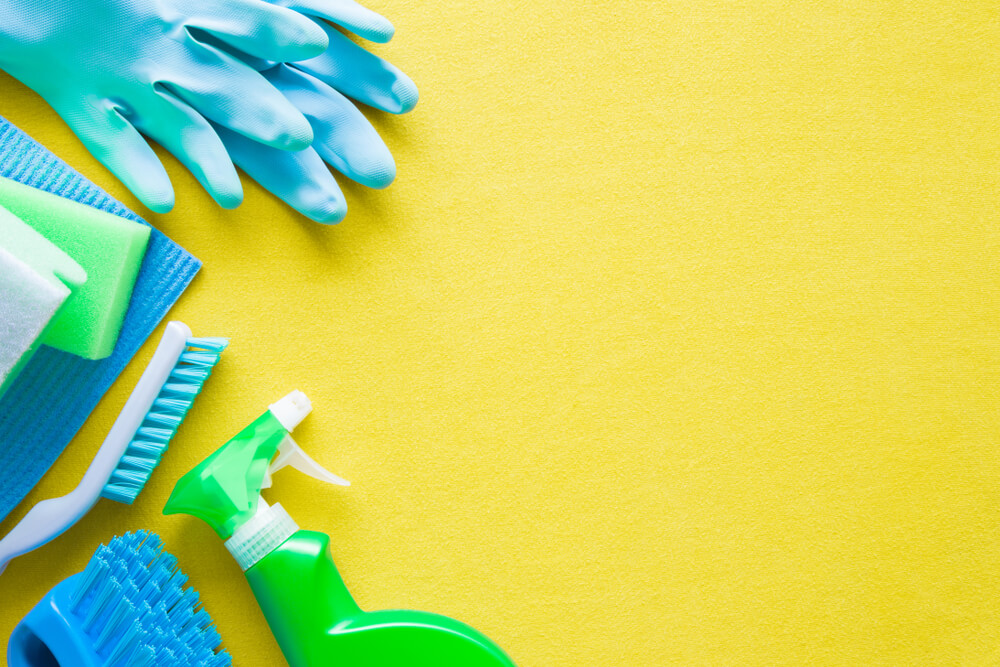 Colorful cleaning set for different surfaces in kitchen, bathroom and other rooms. Empty place for text or logo on yellow background. Cleaning service concept. Early spring regular clean up