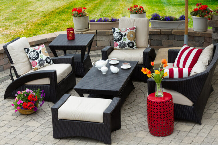 Overview of Upscale Patio Set, Dark Wicker Luxury Furniture with Comfortable Cushions on Outdoor Stone Patio of Affluent Home