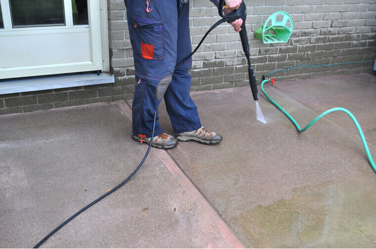 Spring yard work - a man cleaning a sidewalk with a pressure washer. Man cleaning a sidewalk with a pressure washer during spring yard and garden work