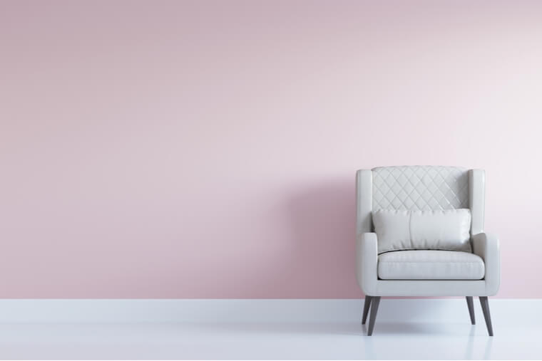White comfortable arm chair in interior living room with pastel pink wall for copy space. Minimal interior