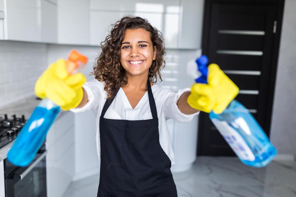 Woman cleaning kitchen. Young woman wearing black apron washing kitchen hood