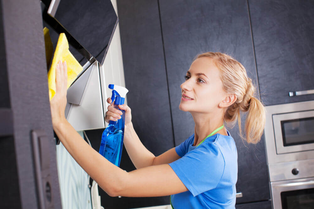 Woman cleaning kitchen. Young woman with blue T-shirt washing kitchen hood