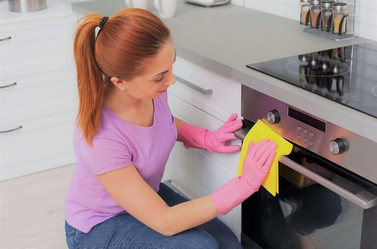 Woman cleaning modern oven with rag in kitchen