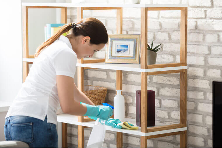 Young Woman Cleaning The Wooden Shelf In Living Room
