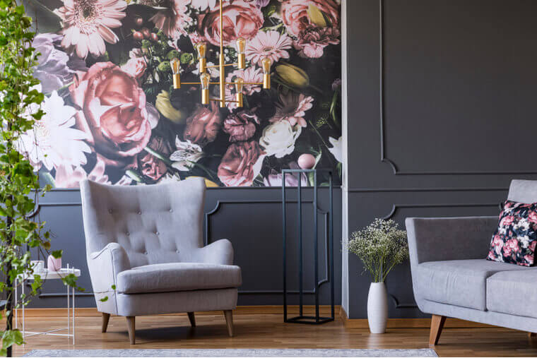 Grey armchair against flowers wallpaper in dark living room interior with sofa and plant