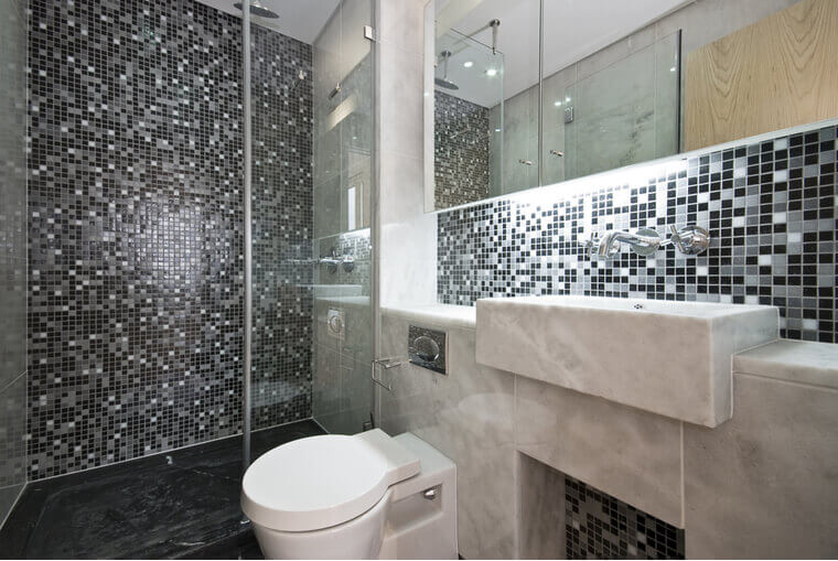 Modern bathroom in black and white with mosaic tiled walls and white ceramic wash basin and toilet