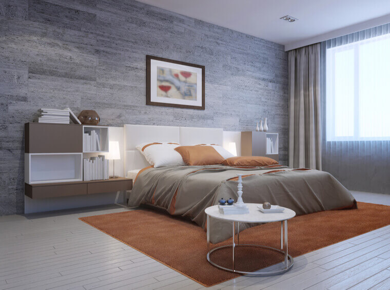 View of modern bedroom interior. Luxury double bed with white headboard and furniture mounted on both sides in white and taupe colors.
