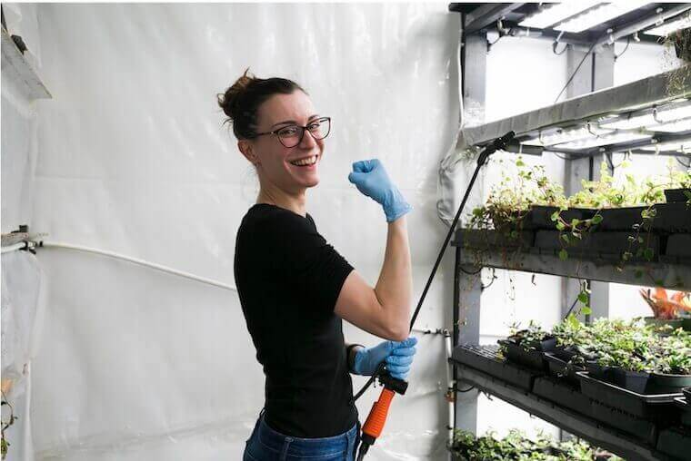 cheerful gardener showing biceps while holding plant spray