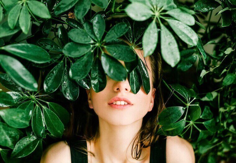 girl smiling with plants around her