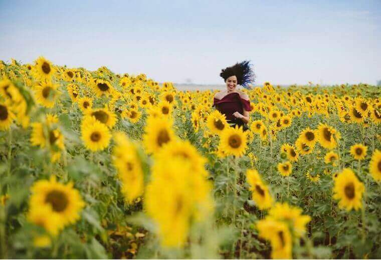 a woman smiling on sunflower field