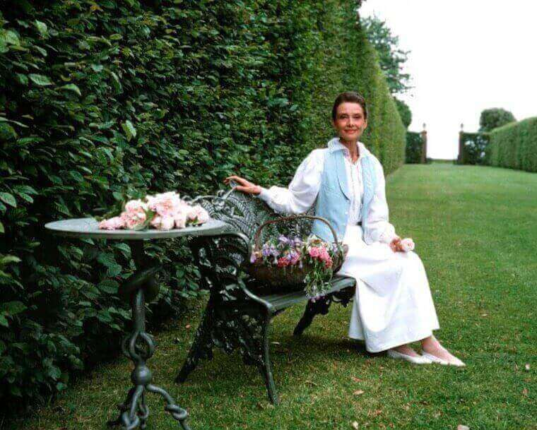 Audrey Hepburn sitting on a bench with a basket of flowers next to her and a table with white roses on top near her