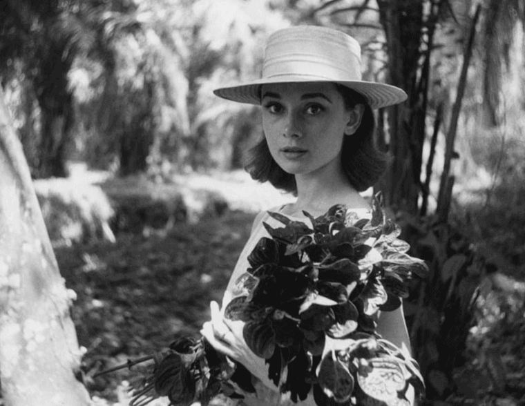 Audrey Hepburn with a hat holding flowers