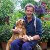 Monty Don holding his dog half on his lap while in a garden