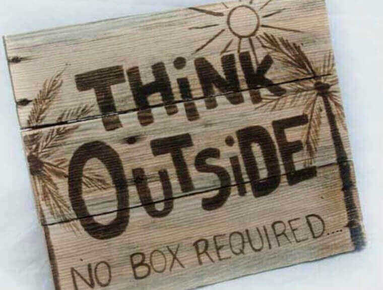 Think outside. No box required' written in wood