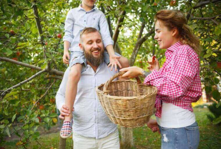 father carrying son over his shoulders with the mother holding a basket