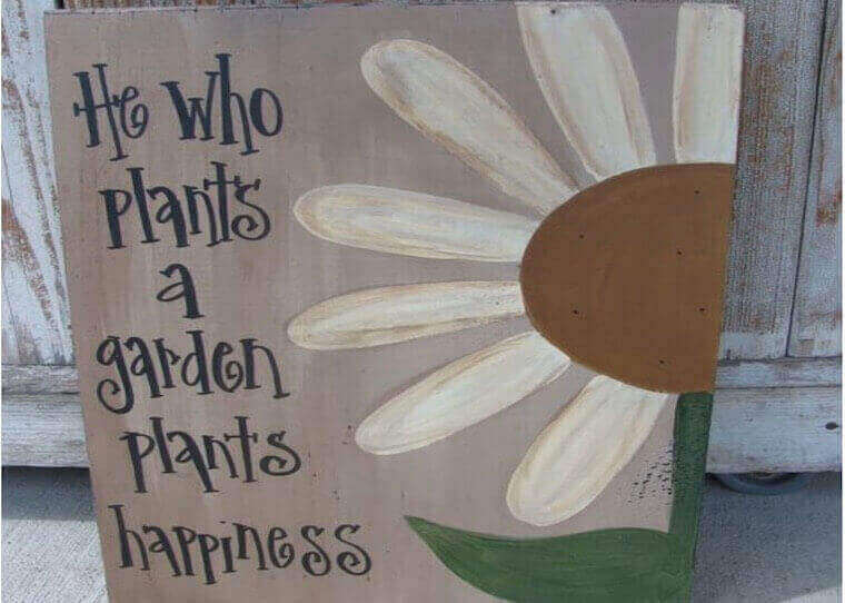 'He who plants a garden plants happiness' written sign with flower drawing on the side