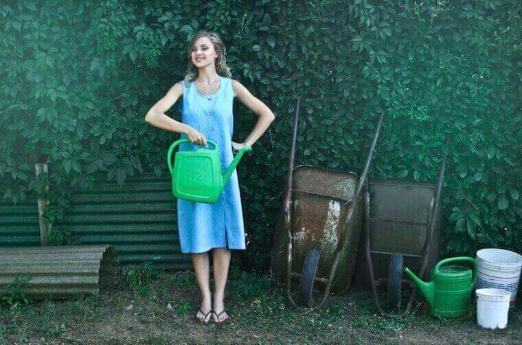 girl in a blue dress holding a watering can in a garden