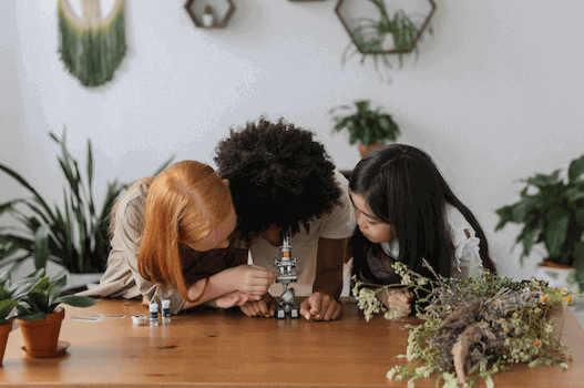 girls looking through a microscope with plants surrounding them