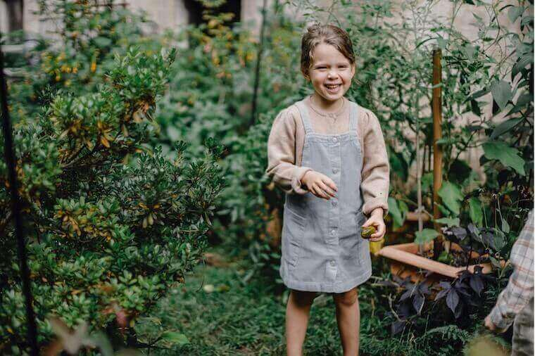happy child smiling while in garden holding a seed