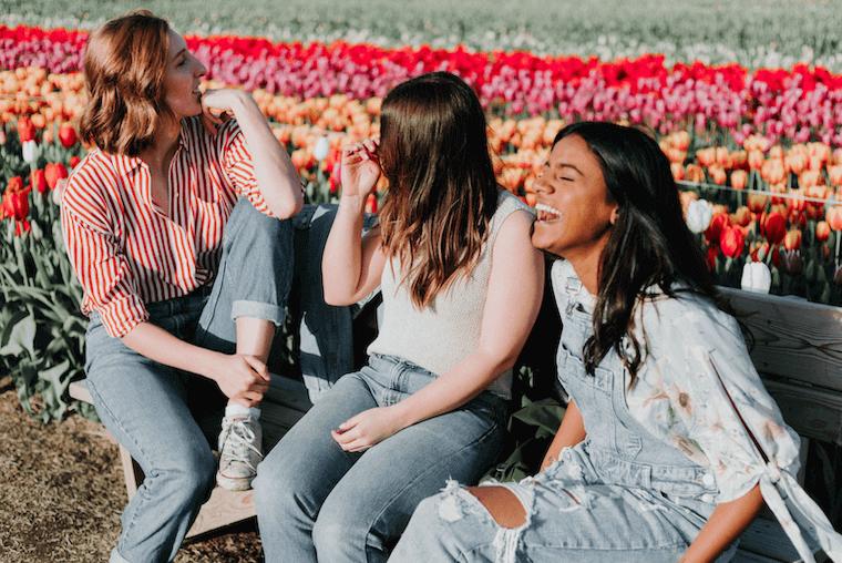 three happy women sitting in a bench next to a tulip garden