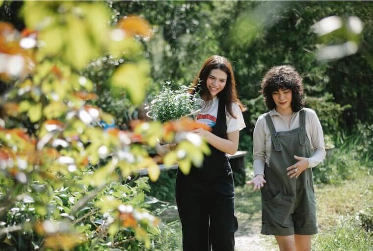 two happy friends walking in a garden