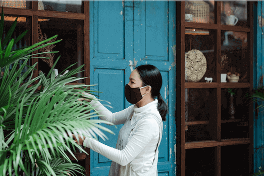 woman with face mask cutting plants with shears
