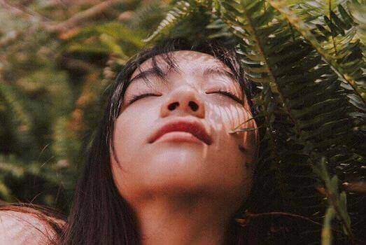 woman with her eyes closed near a fern